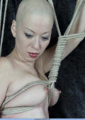 Amateur shaven headed Asian chick is tied up tightly.