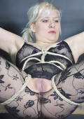 Chaos, is tied to a bondage frame with the most strict rope bondage.