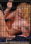 Blond slave trapped inside a dog cage.