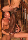 Captivating black whore sucking two huge white cocks on the stairs