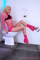 Blond Gloria in pink fishnets and socks sitting on the bowl.