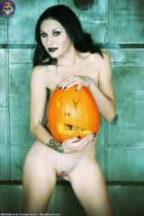 pale gothica girl naked holding big carved pumpkin