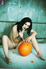 pale gothic girl carving pumpkin