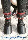 Ponygirl with hoof boots and mistress outdoor.
