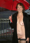 Mature UK woman naked in the steets in a rainy day.